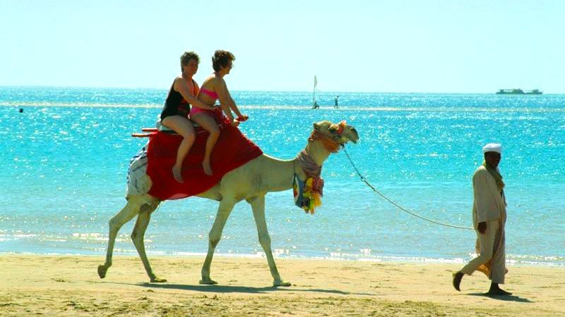 Taking a camel ride on the beach in Hugharda, Egypt